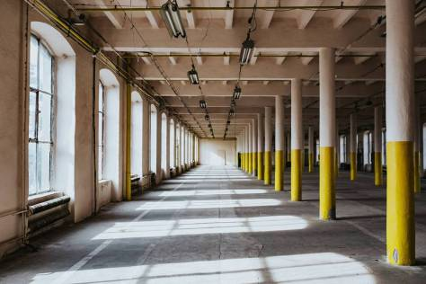Interior of an abandoned building hall with yellow pillars - c